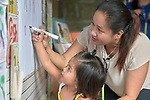 Raquel Fabre, a teacher with the Kapatiran-Kaunlaran Foundation (KKFI), helps a girl trace the letter N in a KKFI-sponsored preschool in Pulilan, a village in Bulacan, Philippines.<br /> <br /> KKFI is supported by United Methodist Women.