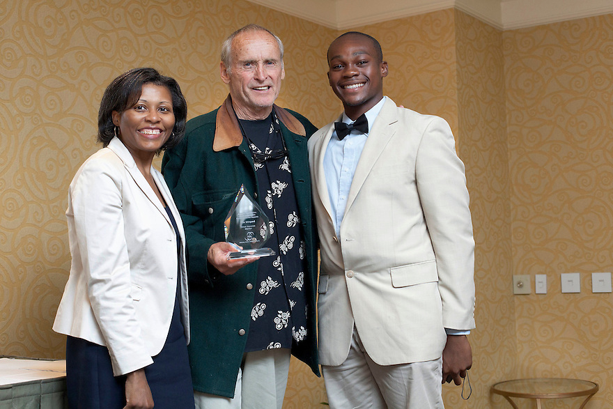 April Hawkins, left, gives Tim Wingard, middle, his award with Giovanni Douresseau, right, at the Older Volunteers Enrich America Awards at the Double Tree Hotel in Washington, DC on Friday, June 17, 2011.