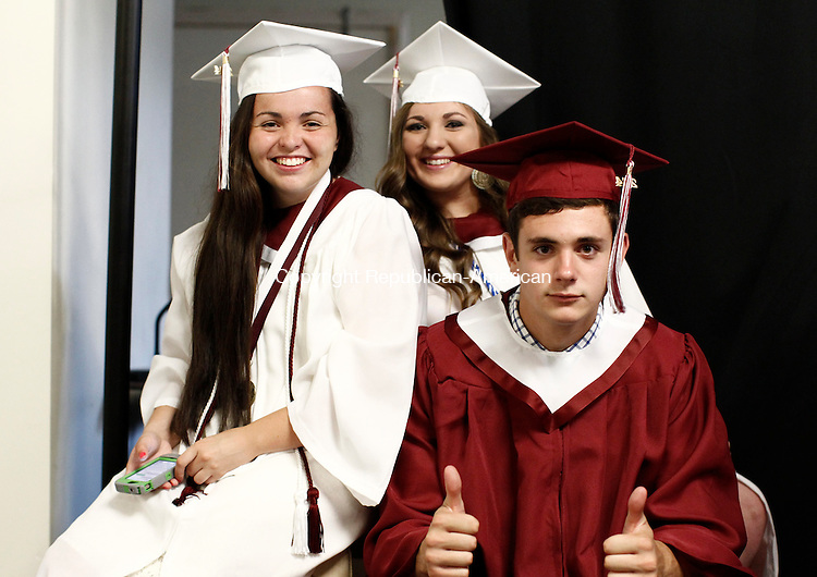 Waterbury, CT- 22 June 2014-062214CM15- Torrington High School graduates, left to right, Samantha Pelow, Griffin Pelkey and Courtney Parsons have some fun before the start of commencement exercises at the Warner Theatre in Torrington on Sunday.  Christopher Massa Republican-American