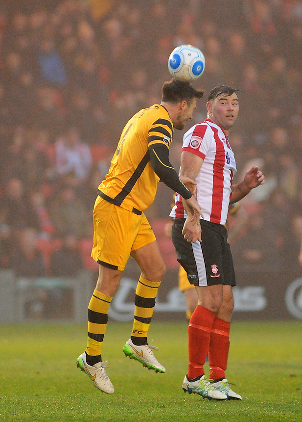 Lincoln City's Matt Rhead vies for possession with Maidstone United's Jamie Coyle<br /> <br /> Photographer Andrew Vaughan/CameraSport<br /> <br /> Vanarama National League - Lincoln City v Maidstone - Saturday 26th November 2016 - Sincil Bank - Lincoln<br /> <br /> World Copyright &copy; 2016 CameraSport. All rights reserved. 43 Linden Ave. Countesthorpe. Leicester. England. LE8 5PG - Tel: +44 (0) 116 277 4147 - admin@camerasport.com - www.camerasport.com