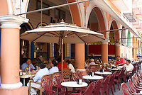 People sitting in one of the sidewalk restaurants under the portales flanking the Plaza de Armas in the city of Veracruz, Mexico