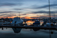 A golden sunset paints the horizon and reflects in the waters of the San Leandro Marina, punctuated by the exclamation-like masts of sail boats and yachts.