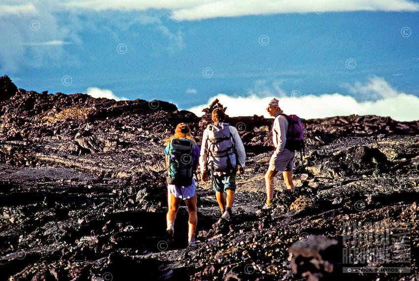 Three hikers climb the hardened lava trail on the slopes of Mauna Loa, Big Island of Hawaii.