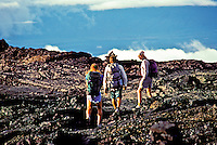 Three hikers climb the hardened lava trail on the slopes of Mauna Loa, Big Island of Hawaii.