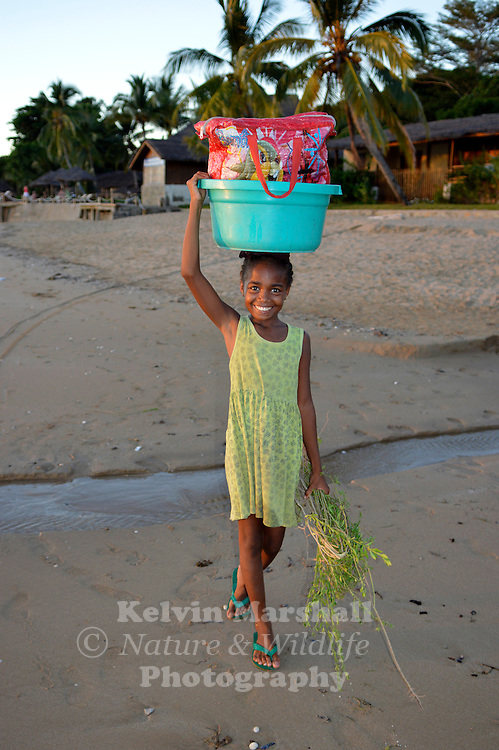 Young Malagasy girl, carrying goods to the market on the beach. Nosy Be, Northern Madagascar.