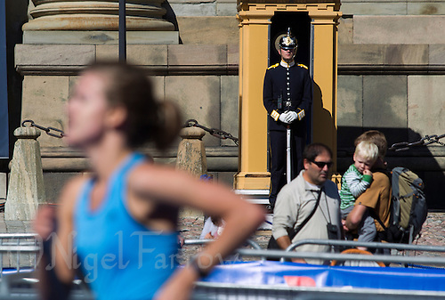25 AUG 2013 - STOCKHOLM, SWE - A member of the Högvakten, the Royal Palace Guards stands on duty as competitors run past during the Stockholm Triathlon in Gamla Stan, Stockholm, Sweden (PHOTO COPYRIGHT © 2013 NIGEL FARROW, ALL RIGHTS RESERVED)