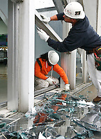 Shaun Jones (L)  and Jacob Caldwell (R), both of Bam Contracting, work on a broken window in the main terminal at Lambert- St. Louis International Airport on April 23, 2011 after storms last night damaged both the interior and exterior of the airport. The airport was closed all day today and officials hope to reopen tomorrow. REUTERS/Sarah Conard (UNITED STATES)