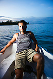 INDONESIA, Mentawai Islands, Kandui Resort, portrait of mid adult man traveling in a small boat at dusk