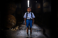 "10 year old Mohamad Aji, second grade student at Kartini Emergency School, stands under the elevated highway where he lives in his makeshift home. Originally from.East Java, Aji's family came to the capital in search of a better life only to end up scavenging to make ends meet. ""When I grow up I want to become a policeman so I can arrest bad people,"" says Aji. Since the early 1990s, twin sisters Sri Rosyati (known as Rossy) and Sri Irianingsih (known as Rian) have used their family inheritance to set up and run 64 schools in different parts of Indonesia, providing primary education combined with practical skills to some of the country's most deprived children."