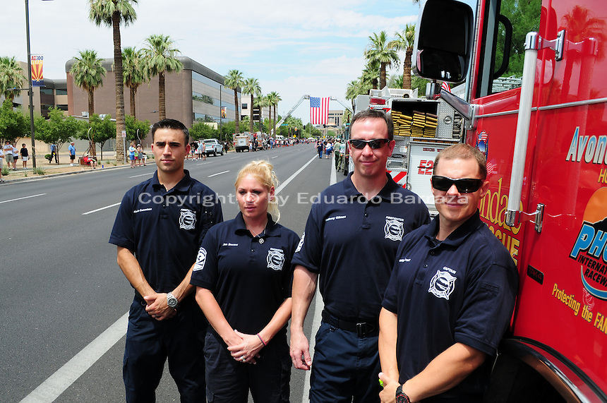 Phoenix, Arizona. July 7, 2013 - Nineteen hearses for each of the fallen members of the Granite Mountain Hotshots Arizona firefighting crew who died last week formed a procession to honor them in Phoenix as their bodies were taken back home to Prescott, about an 80-mile route. Members of the Avondale Fire Department, a suburb of Phoenix, came to pay their respects to their fellow firefighters. From left: Kevin Commisso, Jen Becsei, Anthony Gilman and Captain Justin Ernst, wait for the procession to pass. Photo by Eduardo Barraza © 2013