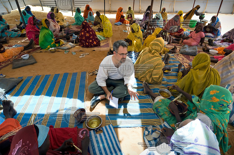 A writer for the Christian Science Monitor, Scott Baldauf, speaks with women in the Zamzam IDP (Internally Displaced Persons) camp near El Fasher, Darfur.