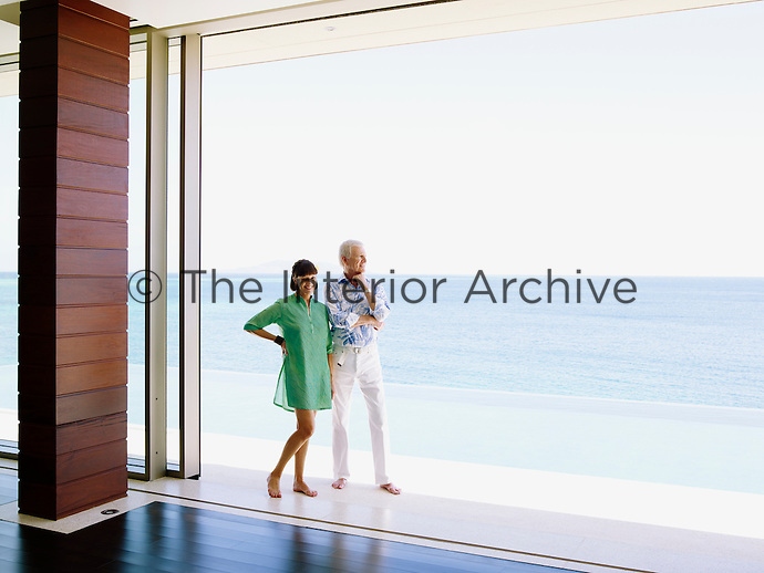 Jill and David Gilmour stand on one of many terraces that surround their beach house which has views over the Koro Sea