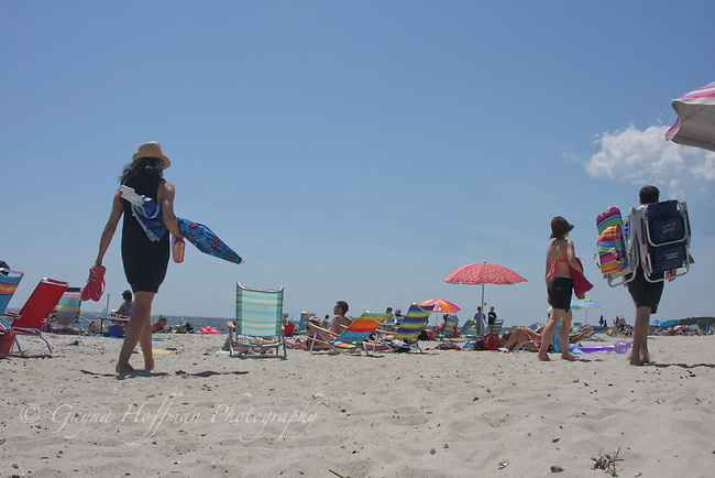 People carrying beach umbrella and chairs to beach.