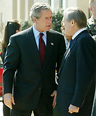 United States President George W. Bush (L) speaks to Secretary of Defense Donald Rumsfeld after a visit to the Pentagon March 25, 2003 in Arlington, Virginia. Bush asked Congress for a wartime supplemental appropriations of $74.7 billion to fund needs directly arising from the war in Iraq and the global war against terror.  <br /> Credit: Alex Wong / Pool via CNP