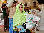 A Rohingya woman carries home a bag of food from an aid distribution by Caritas in the Mainerghona Refugee Camp near Cox's Bazar, Bangladesh, on October 27, 2017. Since August more than 600,000 Rohingya have fled government-sanctioned violence in Myanmar for safety in Bangladesh.