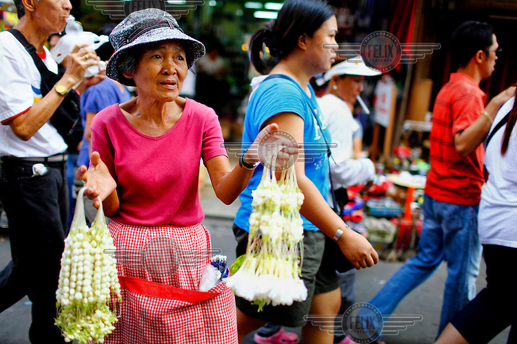 An elderly women sells flower garlands on a busy street.