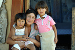"THIS PHOTO IS AVAILABLE AS A PRINT OR FOR PERSONAL USE. CLICK ON ""ADD TO CART"" TO SEE PRICING OPTIONS.   Mirjava Memetovic holds her daughters Kristina (left) and Laura, in front of their makeshift home in Palilula, a neighborhood of Belgrade, Serbia. They are Roma, also known as Gypsies, and were expelled in 2012 from the center of Belgrade to make way for new apartments and office buildings. Because Memetovic had no identity documents, she was sent with her daughters to her native village in the south of the country, but soon returned as she had no way to survive there. She and her daughters beg for money at a fast food restaurant near their squatter settlement."