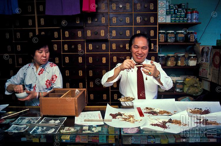 A Chinese herbalist preparing herbal prescriptions in his Chinatown shop in downtown Honolulu