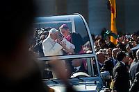 Città del Vaticano. 27 Febbraio, 2013. Papa Benedetto XVI tiene la sua ultima udienza generale il giorno prima delle sue dimissioni da Pontefice, in una Piazza San Pietro gremita di fedeli per l'ultimo saluto. .Il Segretario personale di Benedetto XVI Georg Ganswein porge al Papa un bambino