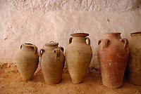 Tunisia, Matmata, terra cotta jars against wall inside troglodyte home