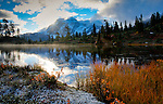 Washington, Cascade Mountains, Picture Lake with autumn colors and fresh snow, reflects Mount Shuksan and the morning sun.