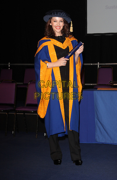Kylie Minogue.Kylie Minogue is made a Honorary Doctor in Health Sciences at the Anglia Ruskin University, Chelmsford, Essex.October 5th, 2011.full length black blue orange graduate robe hat diploma .CAP/ROS.©Steve Ross/Capital Pictures.