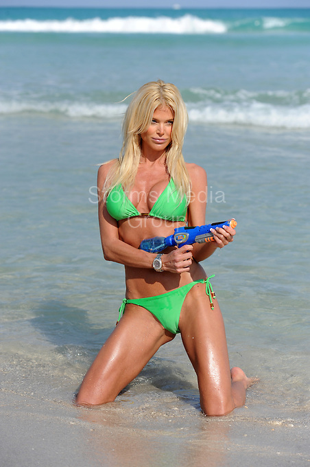"""SMG_EXC_Victoria Silvstedt_GreenBikini_031910_99.JPG_EXCLUSIVE COVERAGE<br /> <br /> MIAMI BEACH, FL-MARCH 19:  (EXCLUSIVE COVERAGE)  Victoria Silvstedt cares about the environment as she  goes """"ALL GREEN"""" in a sexy Bikini on Miami Beach. She enjoyed a day with her friends , playing football,tennis and tanning,  at one point she even grabbed a super soaker water gun and started sraying her friends on the beach.  <br /> <br /> Karen Victoria Silvstedt (born 19 September 1974 in Skellefteå, Västerbotten County), is best known as Victoria Silvstedt,, she is a Swedish model, Playboy Playmate of the Year, actress and singer. She is also a radio and TV hostess, a published singer, and a former national-level skier in Sweden. Silvstedt was already well recognized in the United Kingdom when she took on a new career hosting The Late Show on Virgin Radio, and as a guest host on the TV show Eurotrash. She has appeared on the American TV shows Melrose Place and MTV's The Real World, and she has worked on Italian TV, hosting several shows. She currently co-hosts La Ruota Della Fortuna, the Italian version of Wheel of Fortune on Mediaset's Italia 1, alongside Enrico Papi. As well as its French counterpart, La Roue de La Fortune and Turkish counterpart. She made guest appearances in the Hollywood motion pictures: Boat Trip, The Independent, BASEketball, and Out Cold where she played up to her Swedish-Blonde """"Inga"""" character. Silvstedt is now acting in lead roles in European films mainly based in Italy, and taking to the stage in North America.[3] Silvstedt became a spokesmodel for Guess? Jeans, following in the footsteps of former Guess models, Eva Herzigova, Anna Nicole Smith, and Shana Zadrick. In February 2006 she launched her own lingerie collection during London Fashion Week.[4] As of November 2007 she has been in Italy promoting her new film, Matrimonio alle Bahamas, an Italian comedy starring Massimo Boldi. Silvstedt appears in a reality show centered around her life called"""