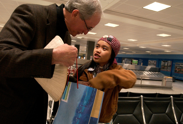 Thuy Anh gives Chuck Atkins a traditional Vietnamese has at Dulles Airport after she arrived from Vietnam.