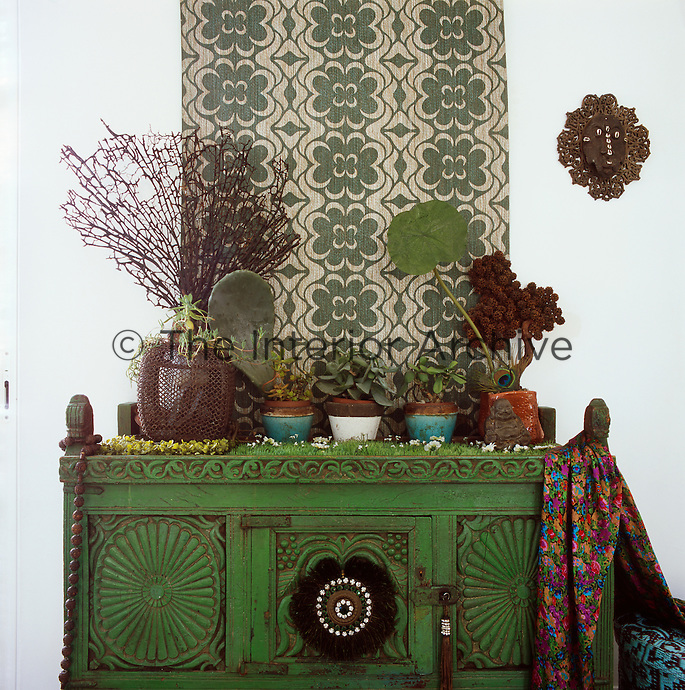 A collection of plants in pots arranged on a green painted cabinet with a patterned wall hanging above, make an interesting focal point in the dining room.