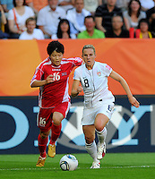 Amy Rodriguez (r) of Team USA and Jong Pok Sim of Team North Korea during the FIFA Women's World Cup at the FIFA Stadium in Dresden, Germany on June 28th, 2011.