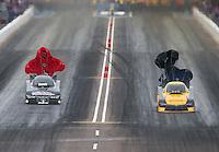 Feb 20, 2015; Chandler, AZ, USA; NHRA funny car driver Del Worsham (right) slows alongside Tony Pedregon during qualifying for the Carquest Nationals at Wild Horse Pass Motorsports Park. Mandatory Credit: Mark J. Rebilas-