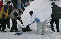 Volunteers shovel snow at a street crossing on Cordova Street to keep snow on the trail during Saturday's ceremonial start.