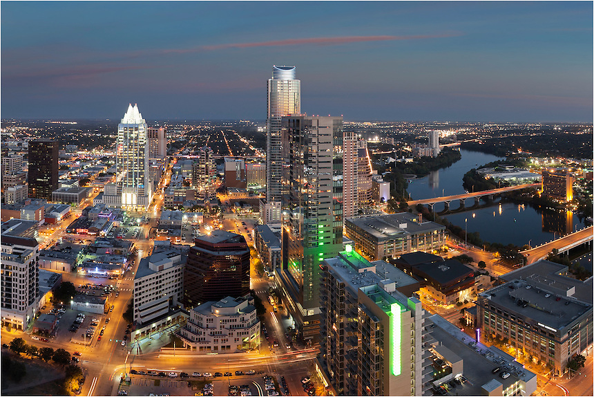 Downtown Austin at night is colorful. This picture of the Austin skyline was taken from atop the 360 Condos building just after sunset. On the left is the Frost Tower. On the right is Lady Bird Lake with the Hyatt Hotel on its south bank.