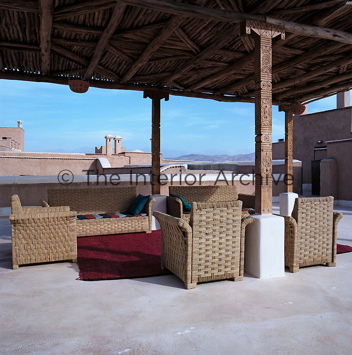 Wicker chairs and sofas afford dramatic views of the Atlas mountains from this sheltered roof terrace