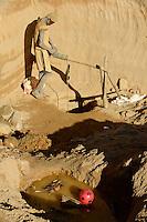 MADAGASCAR, region Manajary, town Vohilava, small scale gold mining / MADAGASKAR Mananjary, Vohilava, kleingewerblicher Goldabbau, Goldsucher GEORGES blaues Shirt, MARIO mit Stirnlampe<br /> und SILVESTRE gelbes Shirt foerdern Steine uind Sand aus einem Stollen, die am Fluss nach Gold gewaschen