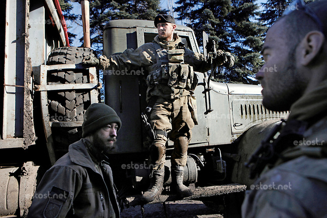 "UKRAINE, 02.2016, Novohrodivka, Oblast Donetsk. Ukrainian-Russian conflict concerning Eastern Ukraine / Foreign volunteers (""Task Force Pluto"") fighting with the far-right militia Pravyi Sektor against the Russian-backed separatists: An Ukrainian militia stands on a truck returning from the frontline to the base of the right-wing organisation. Alex (Austria) and Cowboy (USA) get ready to unload the truck. © Timo Vogt/EST&OST"
