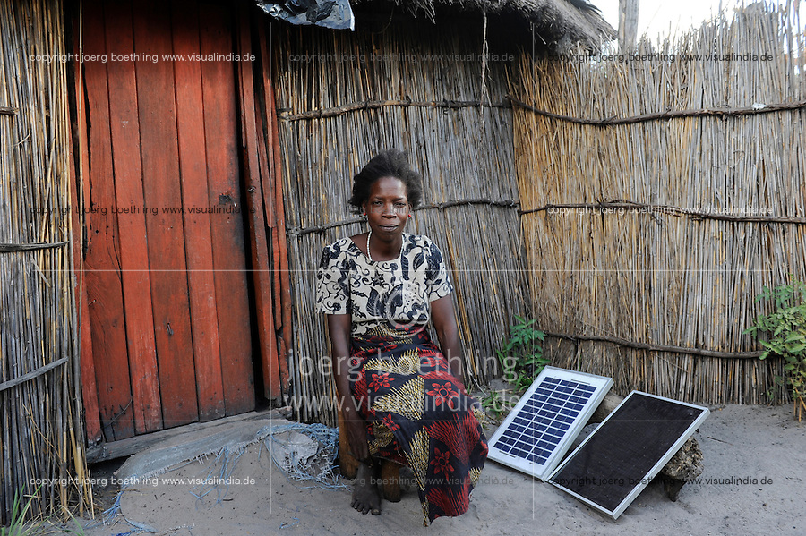 ZAMBIA Barotseland Mongu Lozi village Ilundu, woman with Solare Home System in front of her house /  SAMBIA Barotseland Mongu, Lozi Dorf Ilundu, Frau mit Solar Home system vor ihrem Haus