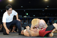 """Yokkoisho"" fights with Yasuhiro Kayahara, AKA ""No Sympathy"". Both wrestlers suffer from cerebral palsy. Referee Shinsuke Funabashi watches on"