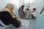 Three-year old Anas, who suffered a severe burn to her chest, is comforted by her mother Ola Yasin and her 8-year old brother Zeki as the girl sits in a therapeutic bath in the Al Ahli Arab Hospital in Gaza City. The girl's grandmother looks on. <br /> <br /> The Anglican Church-affiliated hospital is a member of the ACT Alliance.<br /> <br /> The 2014 war provoked serious damage to Gaza's health infrastructure. Seventeen hospitals, 56 primary health care facilities and 45 ambulances were damaged or destroyed. Sixteen health care workers were killed and 83, most of them ambulance drivers and volunteers, were injured.