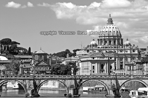 Black and white view of St. Peter's dome and Sant'Angelo bridge in Rome.