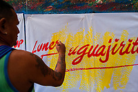 """José Corredor (""""Runner"""") writes with a brush while working on music party posters in the sign painting workshop in Cartagena, Colombia, 12 December 2017. Hidden in the dark, narrow alleys of Bazurto market, a group of dozen young men gathered around José Corredor (""""Runner""""), the master painter, produce every day hundreds of hand-painted posters. Although the vast majority of the production is designed for a cheap visual promotion of popular Champeta music parties, held every weekend around the city, Runner and his apprentices also create other graphic design artworks, based on brush lettering technique. Using simple brushes and bright paints, the artisanal workshop keeps the traditional sign painting art alive."""