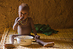 "A small child in the  village of Bele Kwara in southwestern Niger eats ""pot and sauce"" with her hand in the typical traditional African manner. She sits atop a handmade millet stalk bed inside a mud hut."