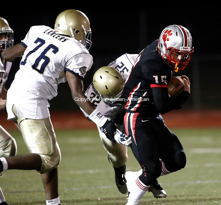 Southbury, CT- 25 November 2014-112514CM21-  Pomperaug's Wade Prajer carries the ball as Notre Dame of Fairfield's William Kelly  (32) and Lynn Nicholas (76) try to make the tackle during their SWC matchup in Southbury on Tuesday.  Christopher Massa Republican-American