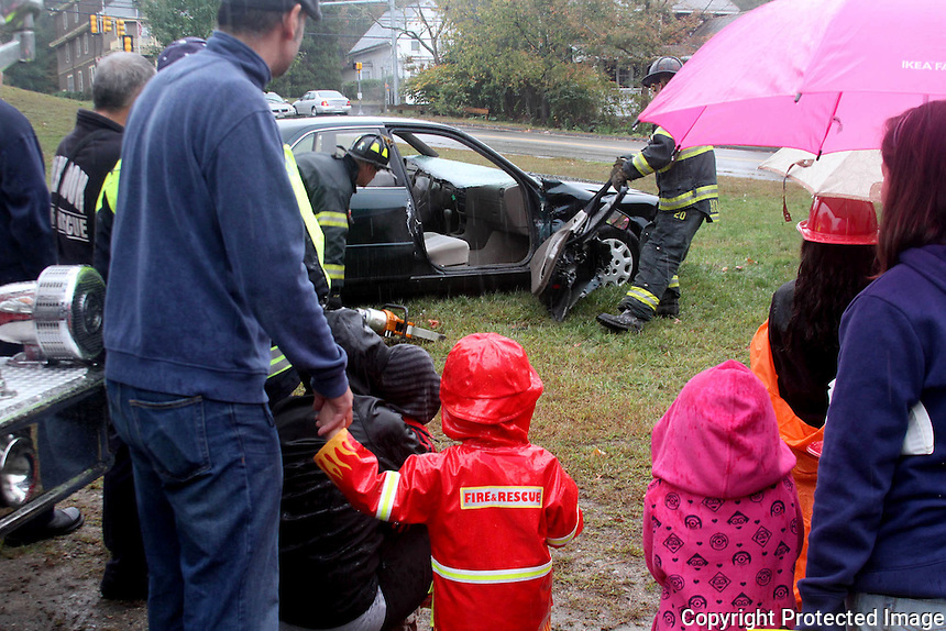Holbrook Fireman show guest how they do a car accident  rescue  during the Holbrook Fire Department open house on Saturday, Oct. 11, 2014.<br /> (Photo by Gary Wilcox)