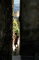 Seven year old boy walking through a very narrow passage, Sartene, Corsica, France.