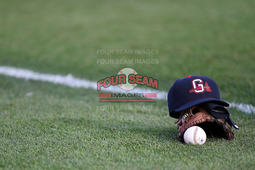 Gwinnett Braves hat, glove and ball in the outfield grass before a game against the Buffalo Bisons on May 13, 2014 at Coca-Cola Field in Buffalo, New  York.  Gwinnett defeated Buffalo 3-2.  (Mike Janes/Four Seam Images)