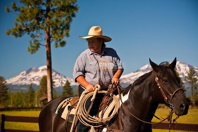 Cowboy (woman) and Three Sisters mountains at R&B Ranch near Sisters, Oregon