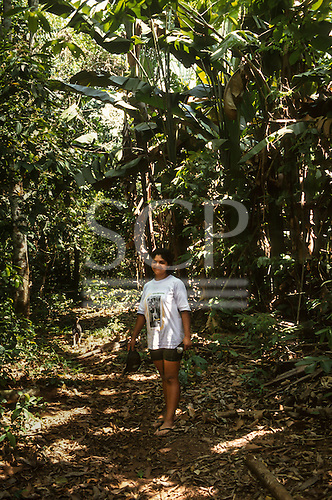 Xapuri, Acre State, Brazil. Woman rubber tapper on a path in the forest.