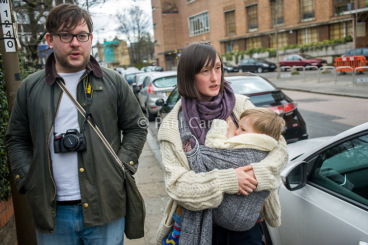 A mother breastfeeds her 15 month old boy from a sling while walking along a city pavement with her partner.<br /> <br /> London, England, UK<br /> 22-03-2015<br /> <br /> © Paul Carter / wdiip.co.uk