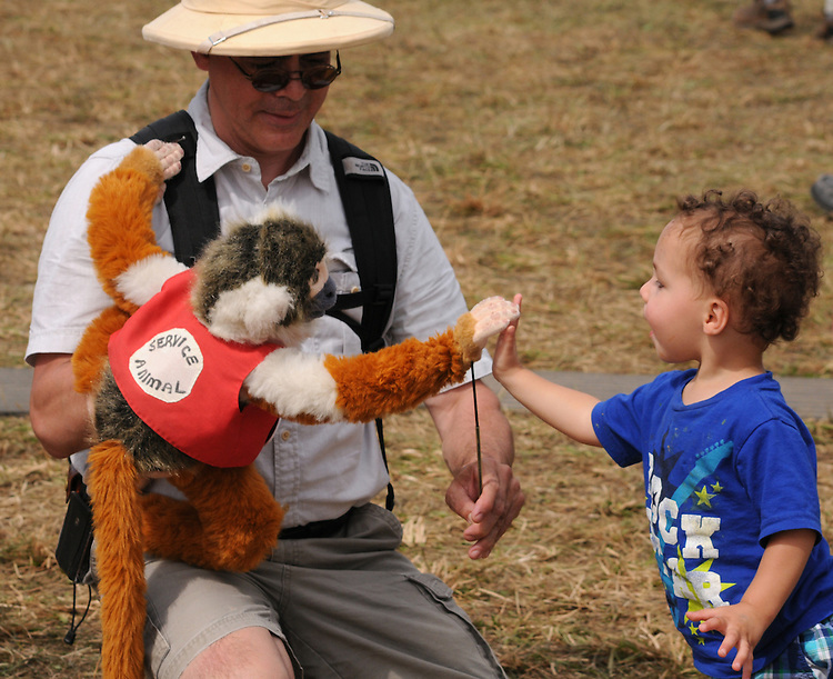 "A child is entertained by a monkey puppet operated by Chris ""Hoopoe"" Yerlig, on the Midway at the Falcon Ridge Folk Festival, held on Dodd's Farm in Hillsdale, NY on Saturday, August 1, 2015. Photo by Jim Peppler. Copyright Jim Peppler 2015."